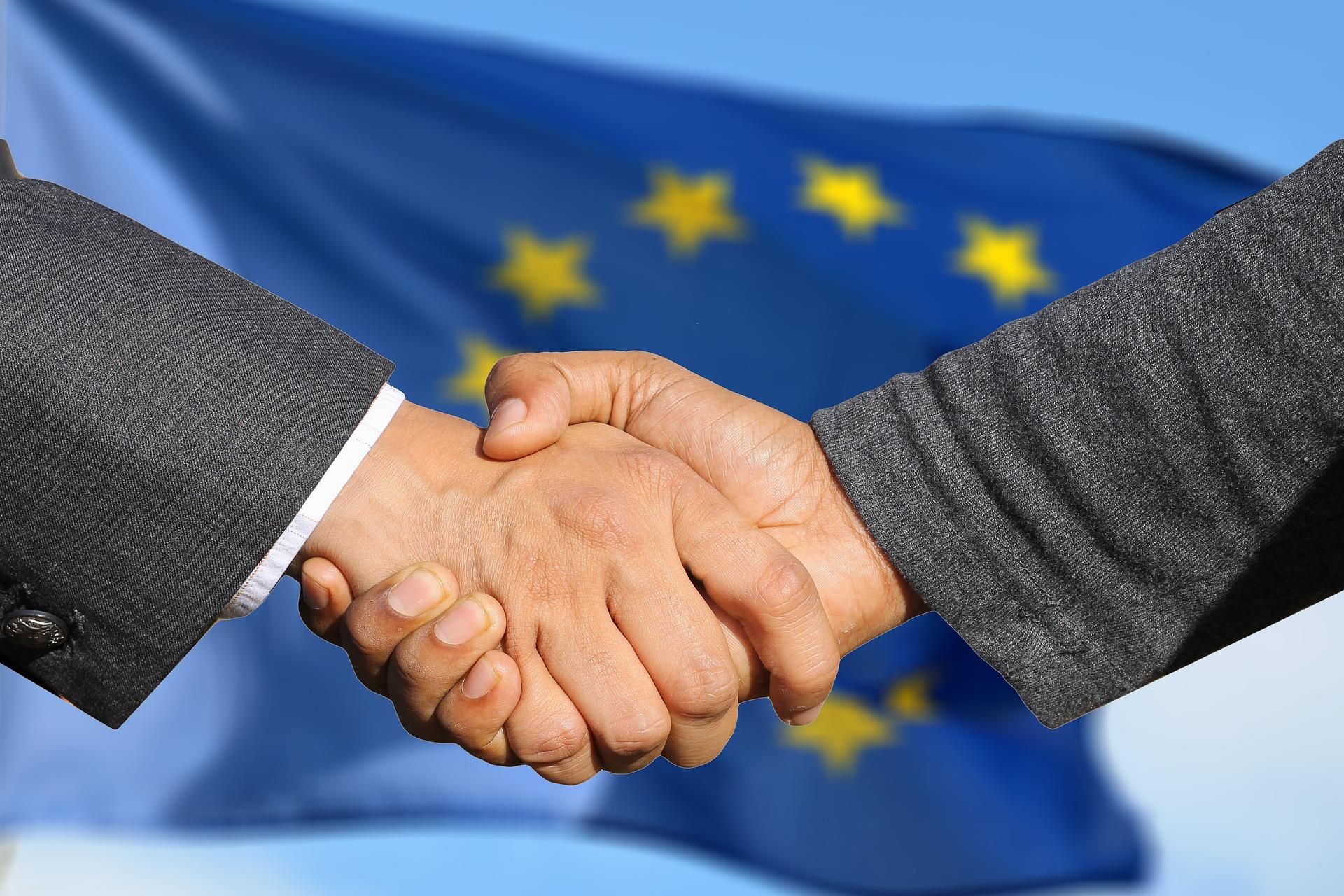 Handslag framför EU-flagga.